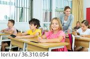Cheerful tween girl listening to schoolteacher and writing in notebook. Стоковое фото, фотограф Яков Филимонов / Фотобанк Лори