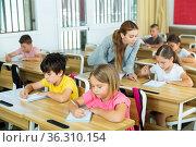 Focused preteen pupils studying in classroom with female teacher. Стоковое фото, фотограф Яков Филимонов / Фотобанк Лори