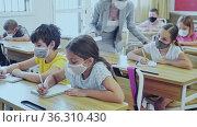 Focused preteen pupils in protective face masks studying in classroom with female teacher. Necessary precautions in coronavirus pandemic. Стоковое видео, видеограф Яков Филимонов / Фотобанк Лори