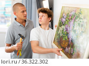 Son helps father to hang the painting on the wall of house. Стоковое фото, фотограф Яков Филимонов / Фотобанк Лори