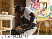 Tired african american male painter at work in art studio. Стоковое фото, агентство Wavebreak Media / Фотобанк Лори
