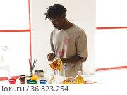 African american male painter at work cleaning hands in art studio. Стоковое фото, агентство Wavebreak Media / Фотобанк Лори
