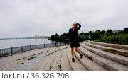 Beautiful young girl posing on the stone steps of a deserted embankment. Стоковое видео, видеограф Момотюк Сергей / Фотобанк Лори