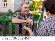 neighbors man and woman chatting near the fence in the village. Стоковое фото, фотограф Татьяна Яцевич / Фотобанк Лори