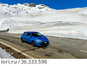 PKW fährt auf der Passtrasse zwischen hohen Schneemauern über den... Стоковое фото, фотограф Zoonar.com/Pant / age Fotostock / Фотобанк Лори