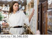 Portrait of woman choosing chest of drawers in furniture store. Стоковое фото, фотограф Яков Филимонов / Фотобанк Лори