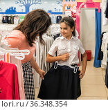 A schoolgirl and her mother in the store choose a skirt, a school uniform. Стоковое фото, фотограф Владимир Ушаров / Фотобанк Лори