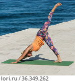 A girl while doing yoga in front of the sea on a sunny summer day. Стоковое фото, фотограф Zoonar.com/Sergio Delle Vedove / age Fotostock / Фотобанк Лори