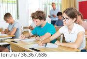 Teenage girl with glasses studying in college with classmates. Стоковое фото, фотограф Яков Филимонов / Фотобанк Лори