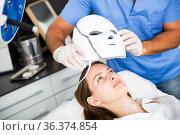 Woman receiving face light therapy in LED mask. Стоковое фото, фотограф Яков Филимонов / Фотобанк Лори