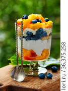 Tiramisu with peach, blueberry and cranberry on wooden background. Стоковое фото, фотограф Марина Володько / Фотобанк Лори