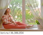 Женщина средних лет сидит на подоконнике и задумчиво смотрит в окно. Стоковое фото, фотограф Ирина Борсученко / Фотобанк Лори