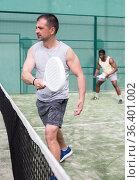 Athletic mens plays padel. View through tennis net. Стоковое фото, фотограф Яков Филимонов / Фотобанк Лори