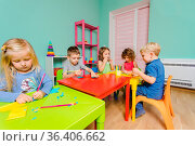 The cute preschoolers sit at the desks in the playroom and draw with... Стоковое фото, фотограф Zoonar.com/OKSANA SHUFRYCH / easy Fotostock / Фотобанк Лори