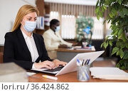 Portrait of a businesswoman in a protective mask, working at a computer in the office. Стоковое фото, фотограф Яков Филимонов / Фотобанк Лори