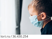 Unhappy young child wearing respiratory mask as prevention against... Стоковое фото, фотограф Zoonar.com/Tomas Anderson / easy Fotostock / Фотобанк Лори