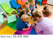 Group of kindergarten kids sitting closely on a floor together with... Стоковое фото, фотограф Zoonar.com/OKSANA SHUFRYCH / easy Fotostock / Фотобанк Лори