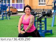 Muscular plump woman performing exercises on the sports ground. Стоковое фото, фотограф Евгений Харитонов / Фотобанк Лори