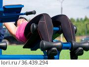 Young woman shakes her press using an outdoor exercise machine abdominal bench. Стоковое фото, фотограф Евгений Харитонов / Фотобанк Лори