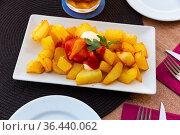 Prepared patatas bravas with sauce served on plate on wooden table. Стоковое фото, фотограф Яков Филимонов / Фотобанк Лори