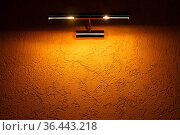 The yellow texture wall is illuminated by a light fixture on top.... Стоковое фото, фотограф Zoonar.com/Sergey Pakulin / easy Fotostock / Фотобанк Лори