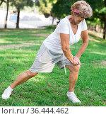 Senior woman stretching outdoors before running in summer park. Стоковое фото, фотограф Татьяна Яцевич / Фотобанк Лори