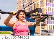 Young woman shakes her triceps using street chest press gym machine. Стоковое фото, фотограф Евгений Харитонов / Фотобанк Лори