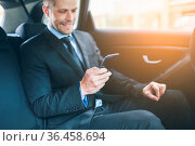 Executive businessman sitting at the back of car using a mobile phone. Стоковое фото, фотограф Zoonar.com/Tomas Anderson / easy Fotostock / Фотобанк Лори