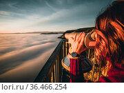 Woman sitting on mountain peak watching sunrise over a sea of fog... Стоковое фото, фотограф Zoonar.com/Maximilian Pawlikowsky / easy Fotostock / Фотобанк Лори