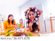 Portrait of cheerful girl looking through decorated Easter wreath... Стоковое фото, фотограф Zoonar.com/OKSANA SHUFRYCH / easy Fotostock / Фотобанк Лори