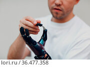 Young disabled man with artificial prosthetic hand put on finger nozzle... Стоковое фото, фотограф Zoonar.com/Max / easy Fotostock / Фотобанк Лори