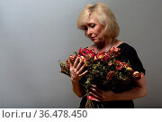 Upset elderly woman hold withered dry old rose flowers bouquet. Стоковое фото, фотограф Zoonar.com/Max / easy Fotostock / Фотобанк Лори