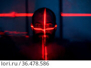 Man in dark with face illuminated by scan red laser on contour. Стоковое фото, фотограф Zoonar.com/Max / easy Fotostock / Фотобанк Лори