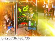 Smiling little mulatto girl aiming laser gun at other players du. Стоковое фото, фотограф Яков Филимонов / Фотобанк Лори