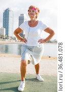 Aged woman doing fitness moves on beach. Стоковое фото, фотограф Татьяна Яцевич / Фотобанк Лори