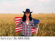 Woman farmer wearing cowboy hat, plaid shirt with american flag at... Стоковое фото, фотограф Zoonar.com/Max / easy Fotostock / Фотобанк Лори