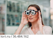 Portrait of happy young woman during eye exam at optometrist optician. Стоковое фото, фотограф Zoonar.com/Max / easy Fotostock / Фотобанк Лори