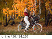 Happy active young woman riding bicycle in autumn park. Стоковое фото, фотограф Zoonar.com/Max / easy Fotostock / Фотобанк Лори