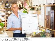 Portrait of attentive man choosing chest of drawers in furniture store. Стоковое фото, фотограф Яков Филимонов / Фотобанк Лори
