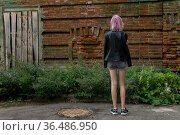 Teenage girl standing alone with her back to the viewer against the background of an old wall. Стоковое фото, фотограф Евгений Харитонов / Фотобанк Лори