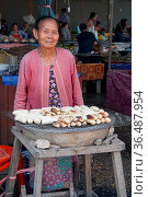 VIENTIANE, LAOS - FEBRUARY 19, 2016: Old woman selling grilled bananas... Стоковое фото, фотограф Zoonar.com/Alexander Ludwig / age Fotostock / Фотобанк Лори