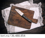 Old brown wooden cutting board with handle and knife on white textile... Стоковое фото, фотограф Zoonar.com/Danko Natalya / easy Fotostock / Фотобанк Лори