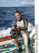 Photographer Franco Banfi on board boat holding camera during sperm whale photography trip Dominica, Caribbean Sea, Atlantic Ocean. 2019. Стоковое фото, фотограф Franco Banfi / Nature Picture Library / Фотобанк Лори
