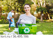 Portrait of smiling caucasian woman holding recycling box, cleaning up countryside with husband. Стоковое фото, агентство Wavebreak Media / Фотобанк Лори