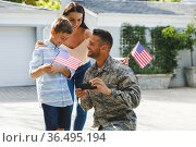 Smiling caucasian male soldier with son and wife outside house with american flags. Стоковое фото, агентство Wavebreak Media / Фотобанк Лори
