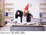 Funny young male employee magician and too much work in the office. Стоковое фото, фотограф Elnur / Фотобанк Лори