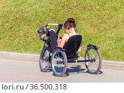 Russia, Samara, June 2021: beautiful athletic girl ride a recumbent bike on the Volga embankment on a summer day. Редакционное фото, фотограф Акиньшин Владимир / Фотобанк Лори