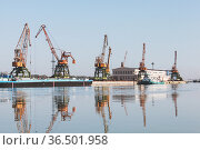 Port cranes stand at the pier in Ruse port, Danube river (2014 год). Стоковое фото, фотограф EugeneSergeev / Фотобанк Лори