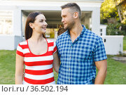 Smiling caucasian couple outside house looking at each other in garden. Стоковое фото, агентство Wavebreak Media / Фотобанк Лори