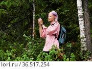 Teenage girl hiker in the forest takes a photo using a smartphone. Стоковое фото, фотограф Евгений Харитонов / Фотобанк Лори